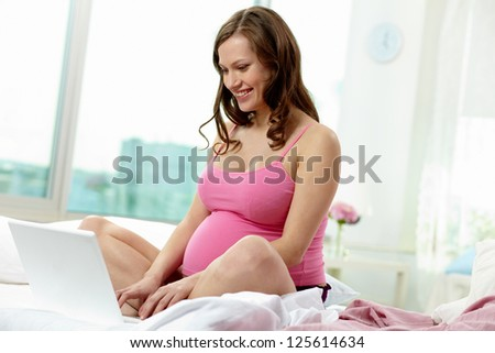 Photo of happy pregnant woman surfing through net - stock photo