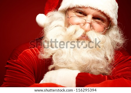 Photo of happy Santa Claus in eyeglasses looking at camera - stock photo
