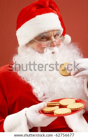 Photo of happy Santa Claus in eyeglasses looking at camera while eating biscuit - stock photo