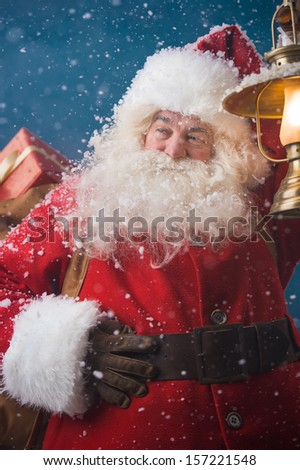 Photo of happy Santa Claus outdoors in snowfall lights the way with vintage lantern while carrying gifts to children