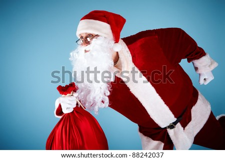 Photo of happy Santa Claus running with red sack - stock photo