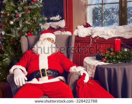 Photo of happy Santa Claus with big bag of presents sleeping at the armchair