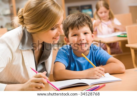 Photo of happy schoolboy looking at camera with teacher near by - stock photo