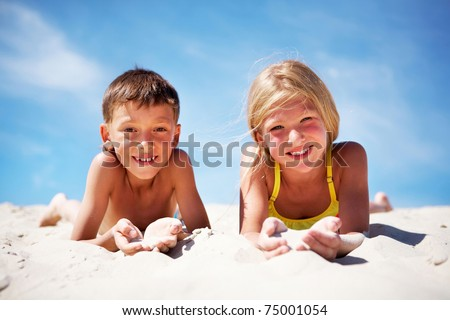 Photo of happy siblings lying on beach and playing with sand on summer vacation - stock photo