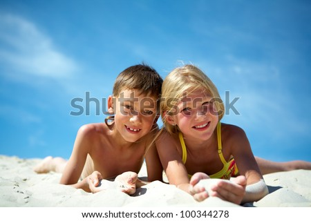 Photo of happy siblings lying on sand and looking at camera
