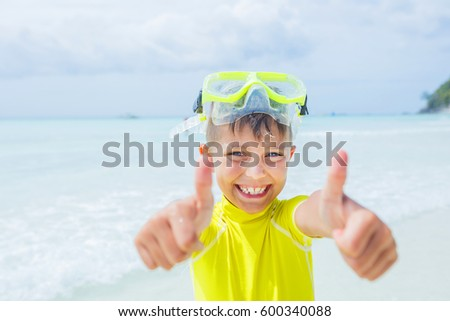 Photo of happy snorkeling boy in yellow swimwear