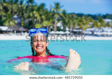 Photo of happy snorkeling girl in pink swimwear