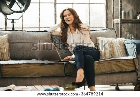 Photo of happy woman in elegant clothing sitting on couch in front open laptop computer in loft living room