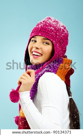 Photo of happy woman in knitted winter cap and scarf posing before camera - stock photo