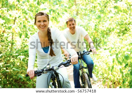 Photo of happy woman riding bicycle outdoors with her husband on background