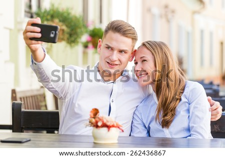 Photo of happy young couple taking a selfie