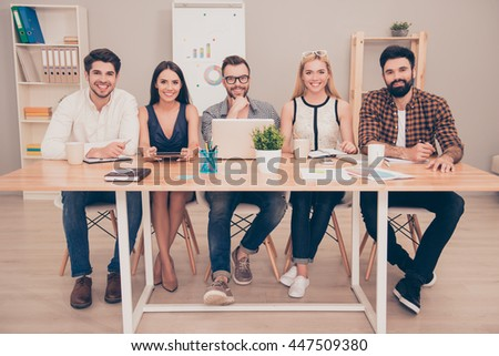 photo of  happy young  group of   businesspeople sitting at conference table smiling - stock photo