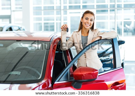 Photo of happy young mixed race woman showing key to her new car. Concept for car rental
