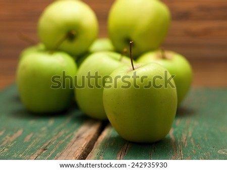 Photo of heap of green apples with one in front which is sharp. All are placed on old wooden board with significant grooves. - stock photo