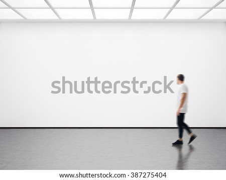 Photo of hipster in modern gallery looking at the empty canvas. Blank mockup, motion blur  - stock photo