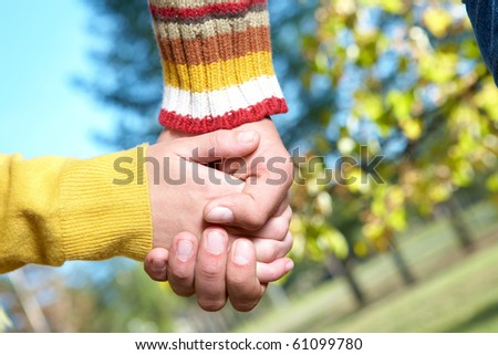 Photo of human hands holding each other outdoors - stock photo