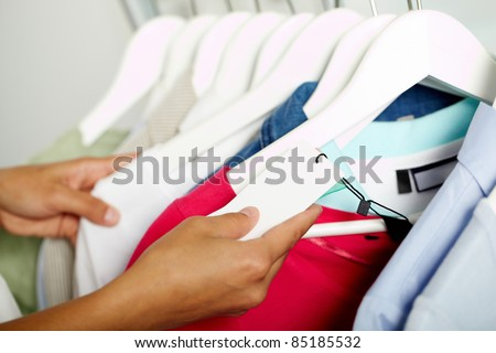 Photo of human hands searching through hangers with clothes - stock photo
