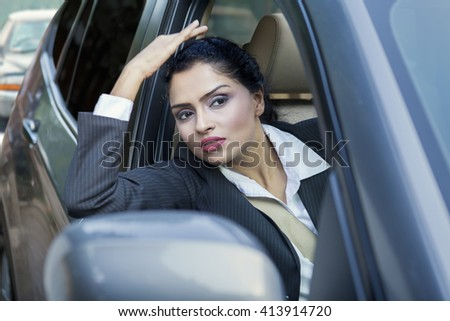 Photo of Indian businesswoman driving a car on the road and looking out the window - stock photo