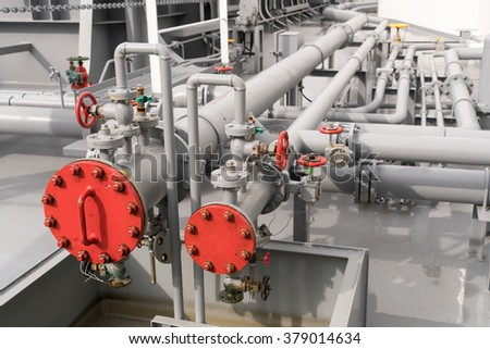 Photo of industrial looking pipes located at eye level with valves.
