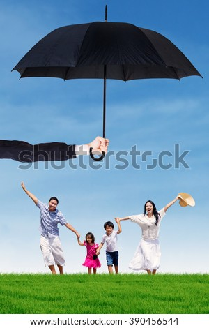 Photo of joyful family running on the meadow while holding hands under umbrella. Life and family insurance - stock photo