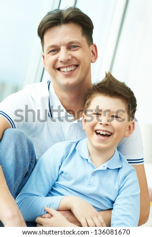 Photo of joyful man embracing his son and both looking at camera - stock photo