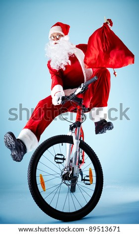 Photo of joyful Santa Claus with red sack on bike looking at camera - stock photo
