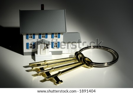 Photo of Keys and a Miniature House - Real Estate Concept