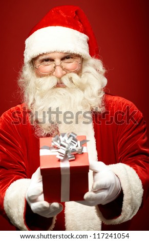 Photo of kind Santa Claus giving xmas present and looking at camera - stock photo