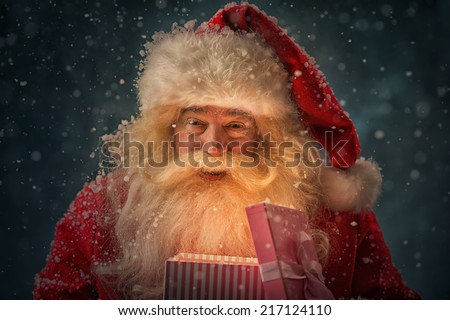 Photo of kind Santa Claus opening and giving xmas present to camera under snowfall - stock photo