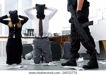 Photo of kneeling businesspeople wearing black sacks on their heads with burglar standing near by - stock photo