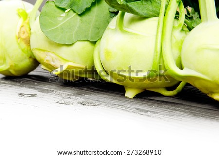 Photo of kohlrabi heads on wooden board with white space - stock photo
