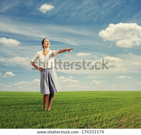 photo of laughing woman pointing at something in the green field