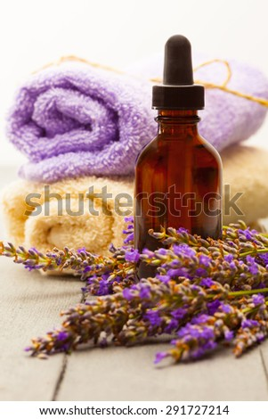 photo of lavender essential oil over wooden table - stock photo