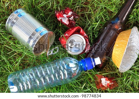 Photo of litter on grass, bottles, cans and wrappers. - stock photo