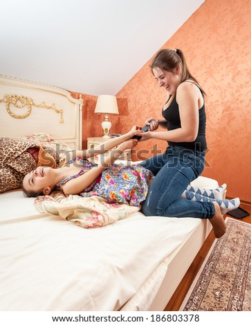 Photo of little and adult sister fighting for TV remote - stock photo