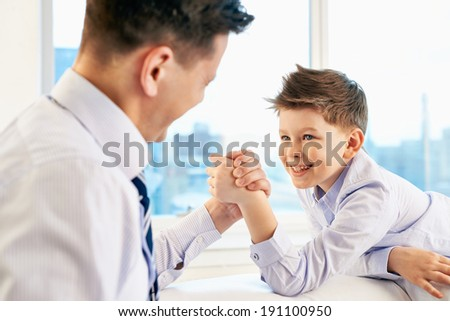Photo of little boy and his dad competing in physical strength - stock photo