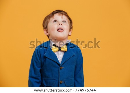 Photo of little boy child standing isolated over yellow background. Looking aside.