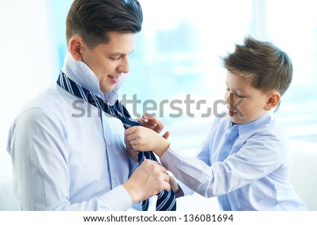 Photo of little boy helping his father tie necktie - stock photo