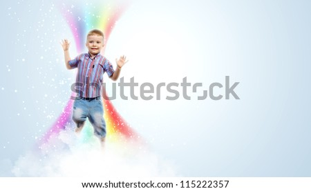 Photo of little boy jumping and raising hands