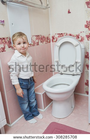 photo of little boy looks in the toilet
