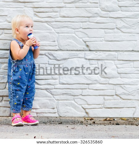Photo of little child with brick wall on the background - stock photo