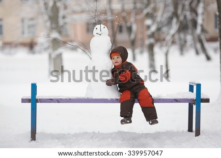 photo of little cute boy with snowman