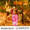 Photo of little cute girl playing in autumn park, adorable sweet kid throwing up old dry foliage, cheerful small female child playing outdoors, nice toddler laughing with closed eyes - stock photo