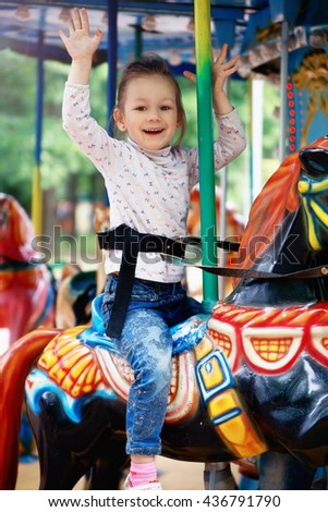 photo of little girl goes for a drive on carousel - stock photo