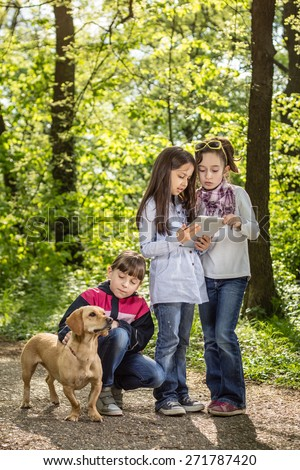 Photo of little girls and the dog having fun in the park - stock photo