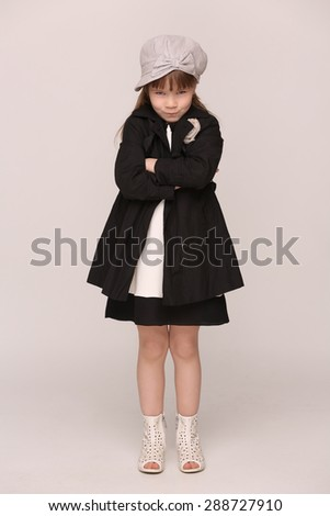 Photo of little groomy girl with her hands clasped. Girl in black coat with bad behaviour posing in full length.  - stock photo