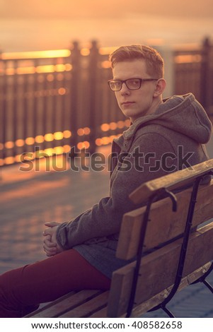 Photo of Lonely Man Sitting on a Bench during Sunset. Portrait of Young Man Sitting on Wooden Bench. Sunset Male Outdoor Portrait