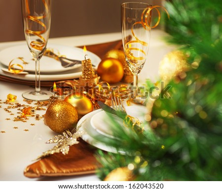 Photo of luxury Christmastime table setting, holiday dinner in restaurant, festive white dinnerware decorated with pretty golden balls and ribbons, warm candle light, green Christmas tree in room - stock photo