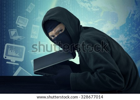 Photo of male person staring at the camera and stealing laptop computer while wearing mask