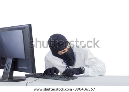 Photo of male robber wearing mask while hacking a computer to steal information, isolated on white background